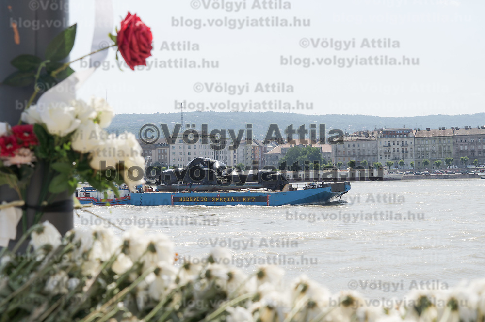 Passenger boat Hableany (means Mermaid in Hungarian) is seen at the location of it's accident surrounded by flowers mourning victims as it is being transported on another boat from the crime scene examination after authorities finished collecting evidences following it's capsize in an accident on river Danube in downtown Budapest, Hungary on June 11, 2019. ATTILA VOLGYI