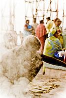 A pilgrim Burning Offerings to the Gods on the ghats during the festival of Kartik Poornima in Varanasi, Uttar Pradesh, India