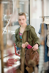 Young woman stealing something in fashion store