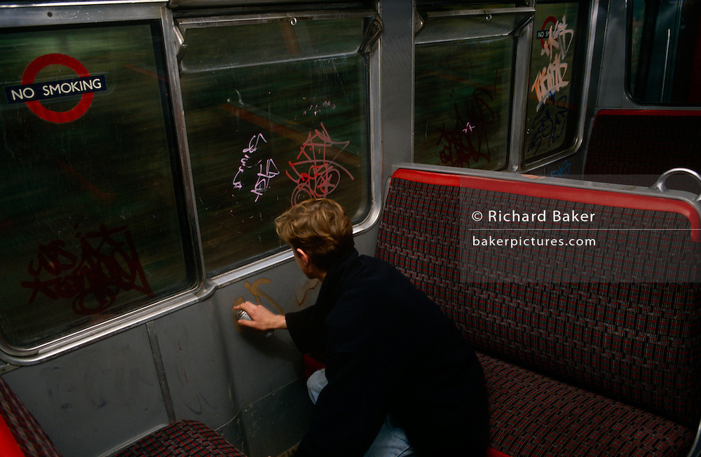 A London youth is busy tagging on windows of a 90s London underground tube train, during an overland section of the capital's rail system near Ladbroke Grove in 1989.