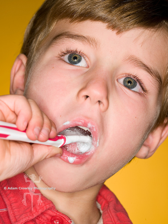 Boy (7 years old) brushes teeth with toothbrush and toothpaste, close up.