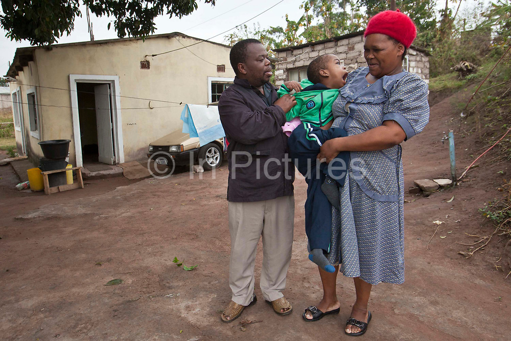 Clement, a South African boy, was born with Cerebral Palsy and lives at home with his parents.  His mother Sbongile is holding him outside their home.  His father is helping.  Durban, KaZulu Natal, South Africa.