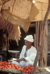 Esna, Egypt:  Fruit seller awaits customers in this village along the Nile.