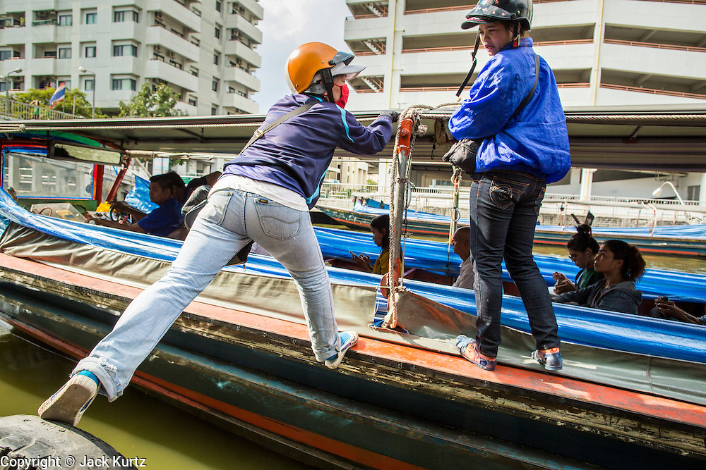 14 NOVEMBER 2012 - BANGKOK, THAILAND: A boat crew boards their boat at the Wat Sriboonreung Pier, the southern terminal of the Khlong Saen Saeb boat service. Bangkok used to be criss crossed by canals (called Khlongs in Thai) but most have been filled in and paved over. Khlong Saen Saeb is one of the few remaining khlongs in Bangkok with regular passenger boat service. Boats and ships play an important in daily life in Bangkok. Thousands of people commute to work daily on the Chao Phraya Express Boats and fast boats that ply Khlong Saen Saeb. Boats are used to haul commodities through the city to deep water ports for export.      PHOTO BY JACK KURTZ