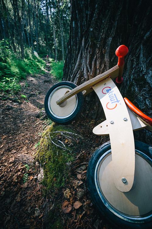Heather Goodrich rides singletrack near Hope Alaska where hikers parked a kid's skuut push bike.