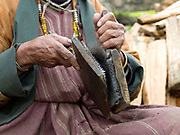 A Brokpa woman carding yak hair before spinning and weaving into cloth in the remote village of Merak in Eastern Bhutan. The Brokpa, the semi-nomads of the villages of Merak and Sakteng are said to have migrated to Bhutan a few centuries ago from the Tshona region of Southern Tibet. Thriving on rearing yaks and sheep, the Brokpas have maintained many of their unique traditions and customs.