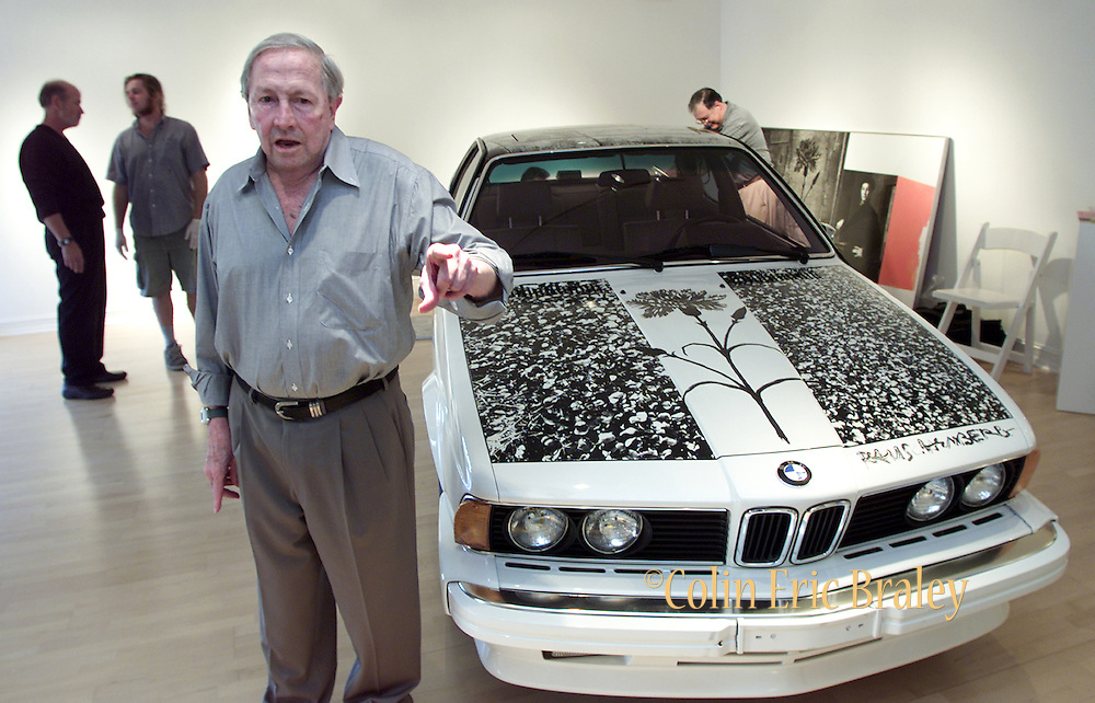 """American pop culture artist Robert Rauschenberg directs the placement of his artwork next to one of his """"Beamer"""" collages at an art gallery in Naples, Florida in this January, 2002, file photo. The 82-year-old died Monday, May 12, 2008, of heart failure according to Jennifer Joy, his representative at PaceWildenstein gallery in New York. Rauschenberg's incorporation of everyday items, both common place and the odd in his artwork earned him the reputation as a pioneering pop artist, gaining fame in the 1950's. Photo by Colin Braley."""
