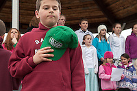 Blake Bolduc of Lee, NH removes his cap and places it over his heart in honor of the victims of Sandy Hook during opening ceremonies for the 26.4.26 relay held on Sunday morning.  (Karen Bobotas/for the Laconia Daily Sun)