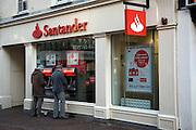 Two men using Santander bank ATM cash point machines