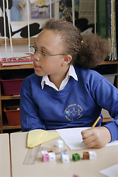 Primary school girl working at desk in practical maths lesson,