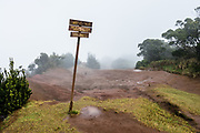 """At Pu'u O Kila Lookout, where the muddy Pihea Trail starts, a sign points to """"Wai'ale'ale, one of the wettest spots on earth, elev 5148 ft"""" which is hidden by fog. Scenic Kokee State Park is in northwestern Kauai in the Hawaiian Islands, USA. Perched on a plateau between 3200 and 4200 feet, the park gets temperatures at least 15 degrees Fahrenheit cooler than at sea level. Koke'e receives 50-100 inches of rain per year, mostly from October to May. Its forests are dominated by Acacia koa and ohia lehua (Metrosideros polymorpha) trees."""