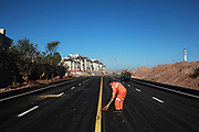 """A man sweeps a newly built road leading towards a luxury housing develpment near the Kangbashi New District of Ordos City, Inner Mongolia, China on 16 August, 2011. With an investment of over 161billion USD from the local government and revenue from the region's rich coal deposits, enough buildings have risen on the site of an old desert village to hold at least 300,000 residents, complete with ultra modern facilities and grand plazas. The district however is less than 10% occupied, dubbed the """"ghost city"""", Kangbashi epitomizes China's real estate bubble and dangers in mindless investment fueled economic  growth. In 2011, the real estate price of Ordos city has dropped over 70%."""