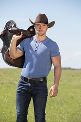 hot cowboy holding a saddle outdoors