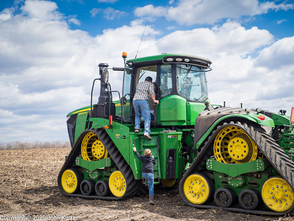 """20 APRIL 2020 - BOUTON, IOWA: A farmer and his son work climb into a tractor to till a field near Bouton. Iowa farmers are prepping their fields for the 2020 season. The relatively mild winter and dry spring has allowed farmers to get into their fields 1 - 2 weeks earlier than last year. Farmers and agricultural workers are considered """"essential"""" workers in Iowa and not subjected to the coronavirus restrictions nonessential workers are. Farmers usually work by themselves, and social distancing guidelines have not impacted them as much as it has workers in Iowa's cities.    PHOTO BY JACK KURTZ"""