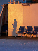 Shadow of man on wall by outdoor heater at sunrise, Havoysund, Norway
