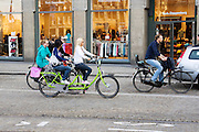 In Amsterdam rijden twee meisjes een beetje angstig op een huurtandem over de Dam tussen het andere verkeer.<br /> <br /> In Amsterdam, two girls riding a little anxious on a rental tandem over the Dam among other traffic.