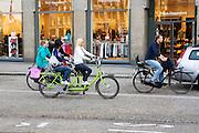 In Amsterdam rijden twee meisjes een beetje angstig op een huurtandem over de Dam tussen het andere verkeer.<br /> <br /> In Amsterdam, two girls riding a little anxious on a rental tandem over the Dam among other traffic.