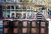 Een man zit op de krantenbakken op de Market Street in San Francisco. De Amerikaanse stad San Francisco aan de westkust is een van de grootste steden in Amerika en kenmerkt zich door de steile heuvels in de stad.<br /> <br /> The US city of San Francisco on the west coast is one of the largest cities in America and is characterized by the steep hills in the city.