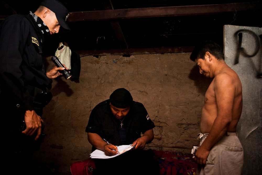 Police interrogate the father of a suspected gangmember and thief during a midnight raid in the country side near San  Salvador.  Constant police pressure in El Salvador is pushing many Maras to the country side where they find it easy to bring disaffected local youths into the gang.