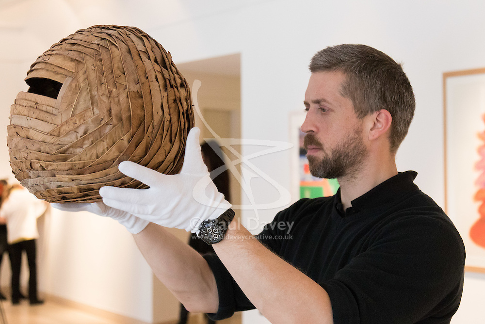 """Christies, St James, London, March 4th 2016. A gallery technician displays Andy Goldsworthy's leafwork """"Sweet Chestnut Leaves and Blackthorns"""" created in Dumfriesshire in 2013, at the preview for the It's Our World charity auction at Christie's. Over 40 leading artists including David Hockney, Sir Antony Gormley, David Nash, Sir Peter Blake, Yinka Shonibare, Sir Quentin Blake, Emily Young and Maggi Hambling have committed artworks to the It's Our World Auction in support of The Big Draw and Jupiter Artland Foundation, to be sold at Christie's London on 10 March 2016.<br />  ///FOR LICENCING CONTACT: paul@pauldaveycreative.co.uk TEL:+44 (0) 7966 016 296 or +44 (0) 20 8969 6875. ©2015 Paul R Davey. All rights reserved."""