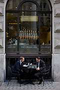Two young businessmen sit outside a deli/cafe laughing over the contents of a laptop in the City of London. The two associates seem to find the subject of their meeting amusing and smile with each other on a street opposite Royal Exchange in the heart of the capital's financial district, founded by the Romans in the 1st Century. In the background we see the lettering on the window of the Italian cafe who boast worldwide locations like Milan, Rome, Turin, London, Tokyo and New York - all presitgious cities for business and fine dining.