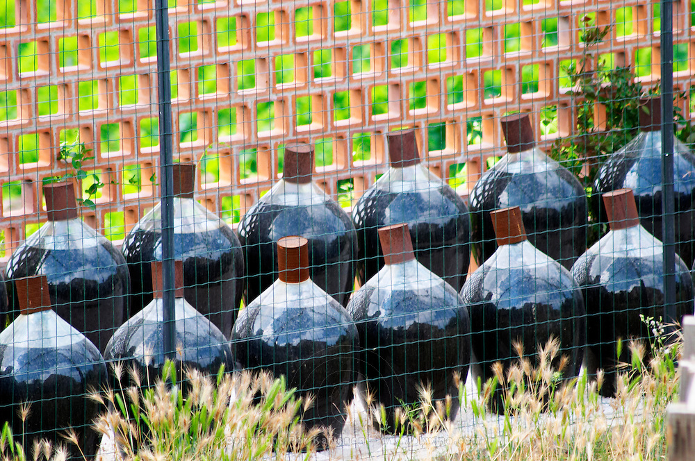 Glass demijohns with Banyuls sweet wine aging outside. Domaine la Tour Vieille. Collioure. Roussillon. Demi-johns with Rivesaltes and Banyuls wine stored outside subject to sun and weather for oxidative aging. France. Europe. Bottle.