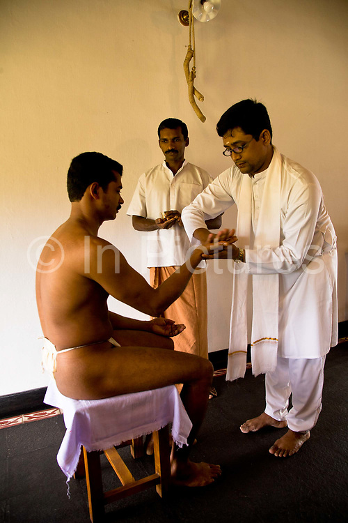 A patient receives Kalari uzhichil as part of the preparatory steps before the full Ayurvedic treatment begins.  Ayurveda is considered a holistic Indian medicine dating back to ancient times, Kollengode, Kerala, India