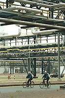 22 MAY 2001, SCHKOPAU/GERMANY:<br /> Zwei Arbeiter sind mit Fahrraedern auf dem weitlaefigen Gelaende der Buna Sow Leuna Olefinverbund GmbH (Dow Chemical Company) unterwegs<br /> IMAGE: 20010522-01/01-06<br /> KEYWORDS: Chemie, chemical, Industrie, industry, Arbeiter, worker, Rohre, Leitungen, Rohrleitungen
