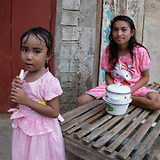 Children eating outside their home in the village of Komodo. Komodo Island, Indonesia.