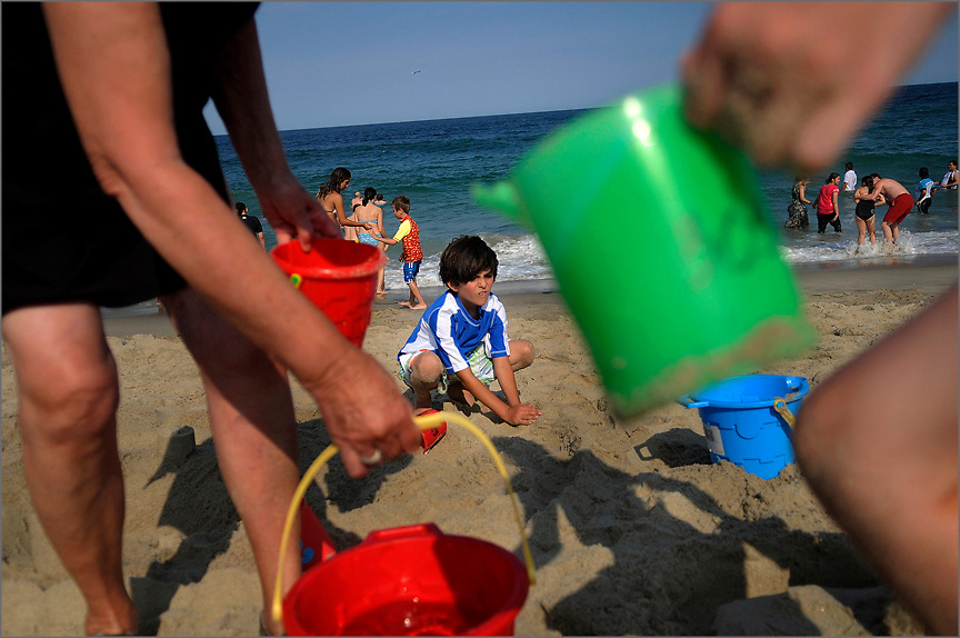 Seven-year old Michael Cavalluzzi (middle) of Eatontown decorates his respective sand castle at Seven President's Oceanfront Park in Long Branch on July 16.  A group of children gathered shells and other treasures then built and decorated their own sandcastles. Photo essay from throughout the Jersey Shore, New Jersey