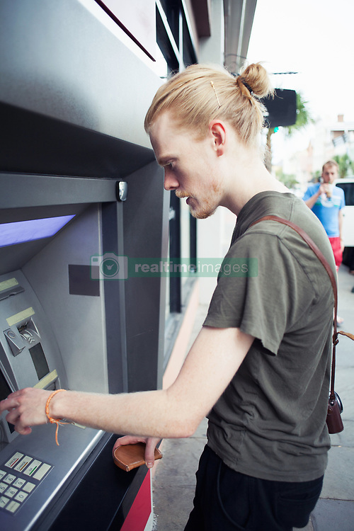 Oct. 7, 2014 - Young man using cash machine (Credit Image: © Image Source/Image Source/ZUMAPRESS.com)