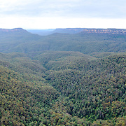 A panorama of the Blue Mountains as seen from Echo Point in Katoomba, New South Wales, Australia. At left is the famous rock formation known as the Three Sisters.