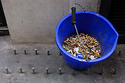 A bucket (pale) of smokers' cigarette butts have been extinguished in a London back street alleyway. Stubbed out in sand to prevent them reigniting for safety reasons, the fags (English slang for cigarettes) echo the steel pegs on the ground. A single packet is also in the bucket at the rear entrance of a London restaurant. Catering staff takes a break from long hours working inside and smoke. The UK government say each year smoking causes 80,000 deaths, costing the National Health Service (NHS) £2.7bn. Just 22% of Britons are smokers - down from 27% at the end of the 1990s - and two-thirds say they would like to give up.