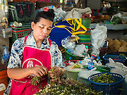 02 SEPTEMBER 2015 - BANGKOK, THAILAND: A vendor sorts herbs in the Bang Chak Market. The Bang Chak Market serves the community around Sois 91-97 on Sukhumvit Road in the Bangkok suburbs. About half of the market has been torn down, vendors in the remaining part of the market said they expect to be evicted by the end of the year. The old market, and many of the small working class shophouses and apartments near the market are being being torn down. People who live in the area said condominiums are being built on the land.         PHOTO BY JACK KURTZ