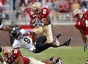 TALLAHASSEE, FL. 10/25/03 -CH 20 FSU-WAKE26 -FSU's Lorenzo Booker, center,  flies over Wake Forest's Caron Bracy and teammate Willie Reid as P.K. Sam, right, watches Saturday during  second half action at Doak Campbell Stadium in Tallahassee...COLIN HACKLEY PHOTO FOR SPORTS SECTION STORY BY CARLSON