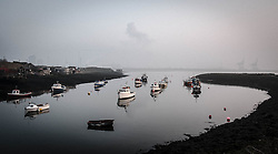 © Licensed to London News Pictures. <br /> 18/03/2015. <br /> <br /> Redcar, Teesside.<br /> <br /> Fishing boats are moored in Paddy's Hole as fog and mist descends over the River Tees in an area known as South Gare near Redcar on Teesside.<br /> <br /> Photo credit : Ian Forsyth/LNP