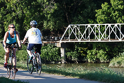Cyclists riding on the Trinity Trails near the Trinity River and train trestle, Fort Worth, Texas, USA.
