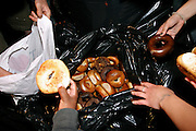 Members of the Freegan community in New York grabbing bagels left in a large bag in front of one of the numerous groceries along 3rd Avenue in Manhattan,  New York, NY., on Wednesday, June 21, 2006. Freegans are a community of people who aims at recovering wasted food, books, clothing, office supplies and other items from the refuse of retail stores, frequently discarded in brand new condition. They recover goods not for profit, but to serve their own immediate needs and to share freely with others. According to a study by a USDA-commissioned study by Dr. Timothy Jones at the University of Arizona, half of all food in the United States is wasted at a cost of $100 billion dollars every year. Yet 4.4 million people in the United States alone are classified by the USDA as hungry. Global estimates place the annual rate of starvation deaths at well over 8 million. The massive waste generated in the process fills landfills and consumes land as new landfills are built. This waste stream also pollutes the environment, damages public health as landfills chemicals leak into the ground, and incinerators spew heavy metals back into the atmosphere. Freegans practice strategies for everyday living based on sharing resources, minimizing the detrimental impact of our consumption, and reducing and recovering waste and independence from the profit-driven economy. They are dismayed by the social and ecological costs of an economic model where only profit is valued, at the expense of the environment. In a society that worships competition and self-interest, Freegans advocate living ethical, free, and happy lives centred around community and the notion that a healthy society must function on interdependence. Freegans also believe that people have a right and responsibility to take back control of their time.