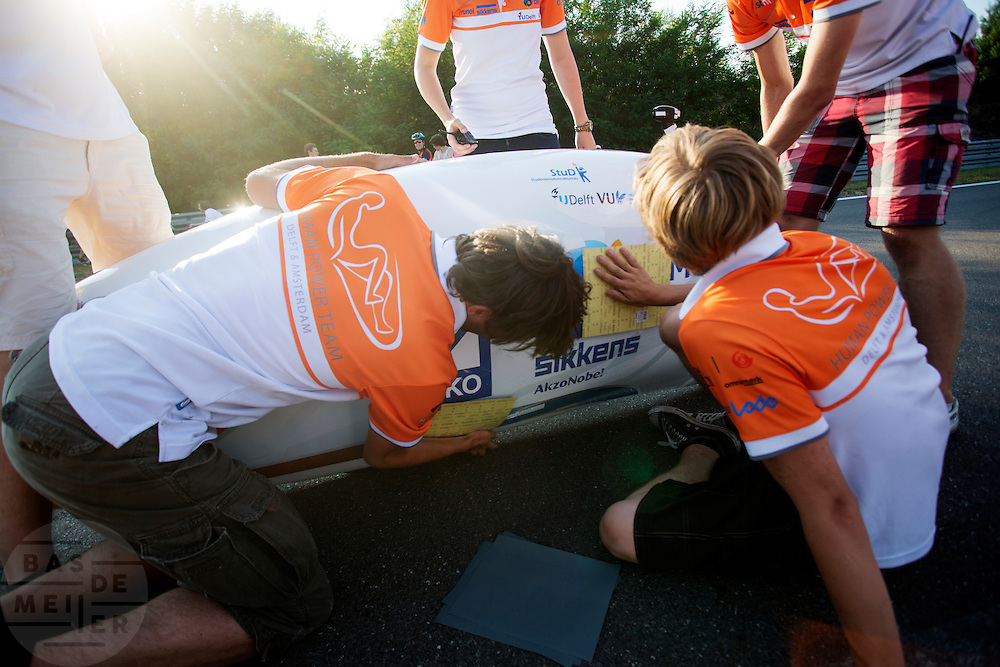 De beschadigingen na de val worden bijgewertk met schuurpapier. In Lausitz rijdt Wil Baselmans van het Human Power Team Delft en Amsterdam de eerste poging om het uurrecord te breken. Wegens warmte heeft hij zijn poging na een half uur moeten afbreken. In september wil het team, dat bestaat uit studenten van de TU Delft en de VU Amsterdam, een poging doen het wereldrecord snelfietsen te verbreken, dat nu op 133 km/h staat tijdens de World Human Powered Speed Challenge.<br /> <br /> The damages after the crash are repaired just for the second start. At the Dekra test track in Lausitz Wil Baselmans of the Human Power Team Delft and Amsterdam is riding his first attempt to set a new hour record with the VeloX3. After half an hour Baselmans has to stop due to the heat. With the special recumbent bike the team, consisting of students of the TU Delft and the VU Amsterdam, also wants to set a new world record cycling in September at the World Human Powered Speed Challenge. The current speed record is 133 km/h.