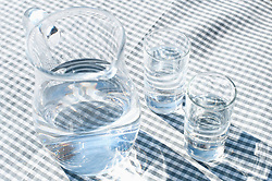 Mug of water with two glasses on dining table, Zillertal, Tyrol, Austria