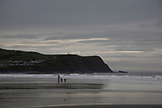 Woman walking her dogs on the beach at seaside town of Borth on a grey gloomy day in Wales, United Kingdom.