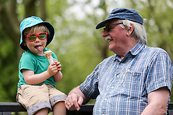 © Licensed to London News Pictures. 07/06/2021. London, UK. Grandad, Kevin, looks at two and half year old, Felix who is enjoying an ice cream, in Finsbury Park, north London, as the warm weather continues in the capital. According to the Met Office, a high of 24 degrees celsius is forecast for London and South East of England. <br /> <br /> ***Permission Granted***<br /> <br /> Photo credit: Dinendra Haria/LNP