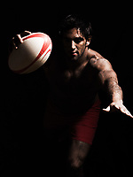 one caucasian sexy topless man scoring touchdown with  a rugby ball on studio black background