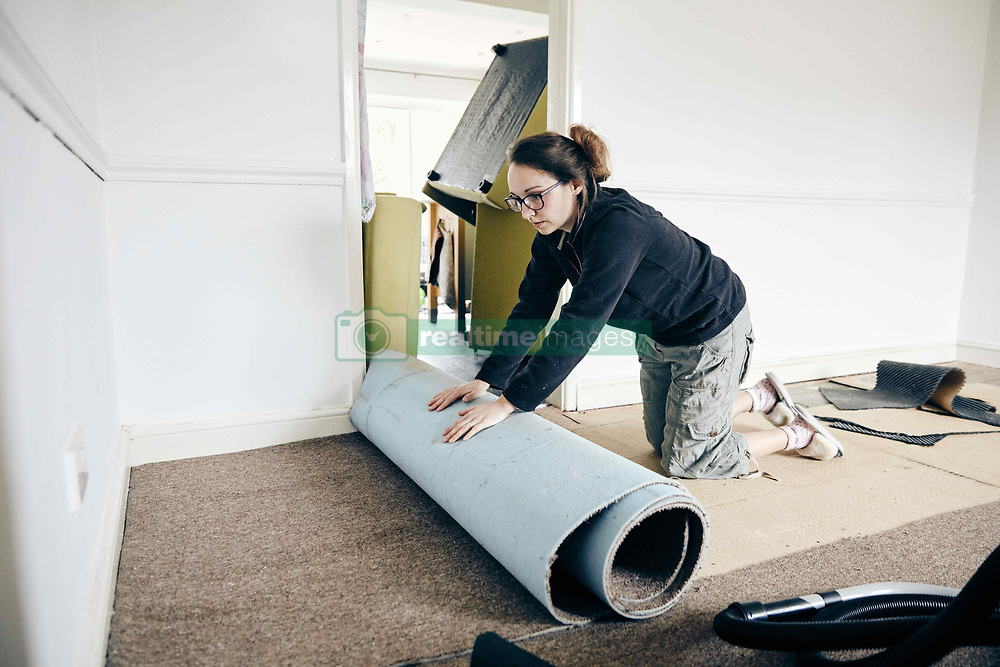 February 14, 2018 - Woman rolling up old carpet in preparation to renew flooring (Credit Image: © Mint Images via ZUMA Wire)