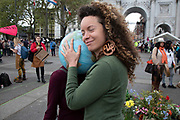 Climate change activists from the Extinction Rebellion group at the Marble Arch camp wears a globe of the Earth on her head as another protester hugs the planet in protest that the government is not doing enough to avoid catastrophic climate change and to demand the government take radical action to save the planet, on 24th April 2019 in London, England, United Kingdom. Extinction Rebellion is a climate change group started in 2018 and has gained a huge following of people committed to peaceful protests.