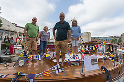 © Licensed to London News Pictures.  03/09/2021. London, UK. Andrew Jenkinson (L) with his wife Caroline and Andrew Clements with his wife Jane pose for a photo on their boat Glitterwake at St Katharine Docks Marina on the River Thames ahead of the Classic Boat Festival this weekend. With 40 vintage sail and motor yachts, the Classic Boat Festival is part of Totally Thames' 25th festival. Photo credit: Marcin Nowak/LNP