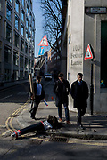 Avoiding the obstacle and potential public liability insurance claim, young men walk past a damaged bollard, knocked over by a reversing vehicle, on 13th February 2017, in the City of London, United Kingdom.