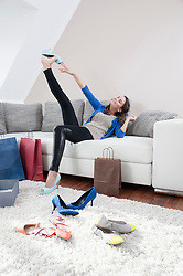 Young happy woman sitting on couch at home with her new high heels