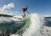Claudia Cantin rides the wave off the back of the boat during an evening of wake surfing on Lake Winnisquam with her family.  (Karen Bobotas/for the Laconia Daily Sun)