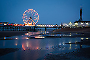 The Blackpool Big Wheel lit-up at dusk on Central Pier, Blackpool, Lancashire, England, United Kingdom.  Designed by John Isaac Mawson and opened in 1868, of the three piers, the Central Pier's emphasis is on fun. The lights from the pier reflect in the sea water on the beach. <br /> (photo by Andrew Aitchison / In pictures via Getty Images)